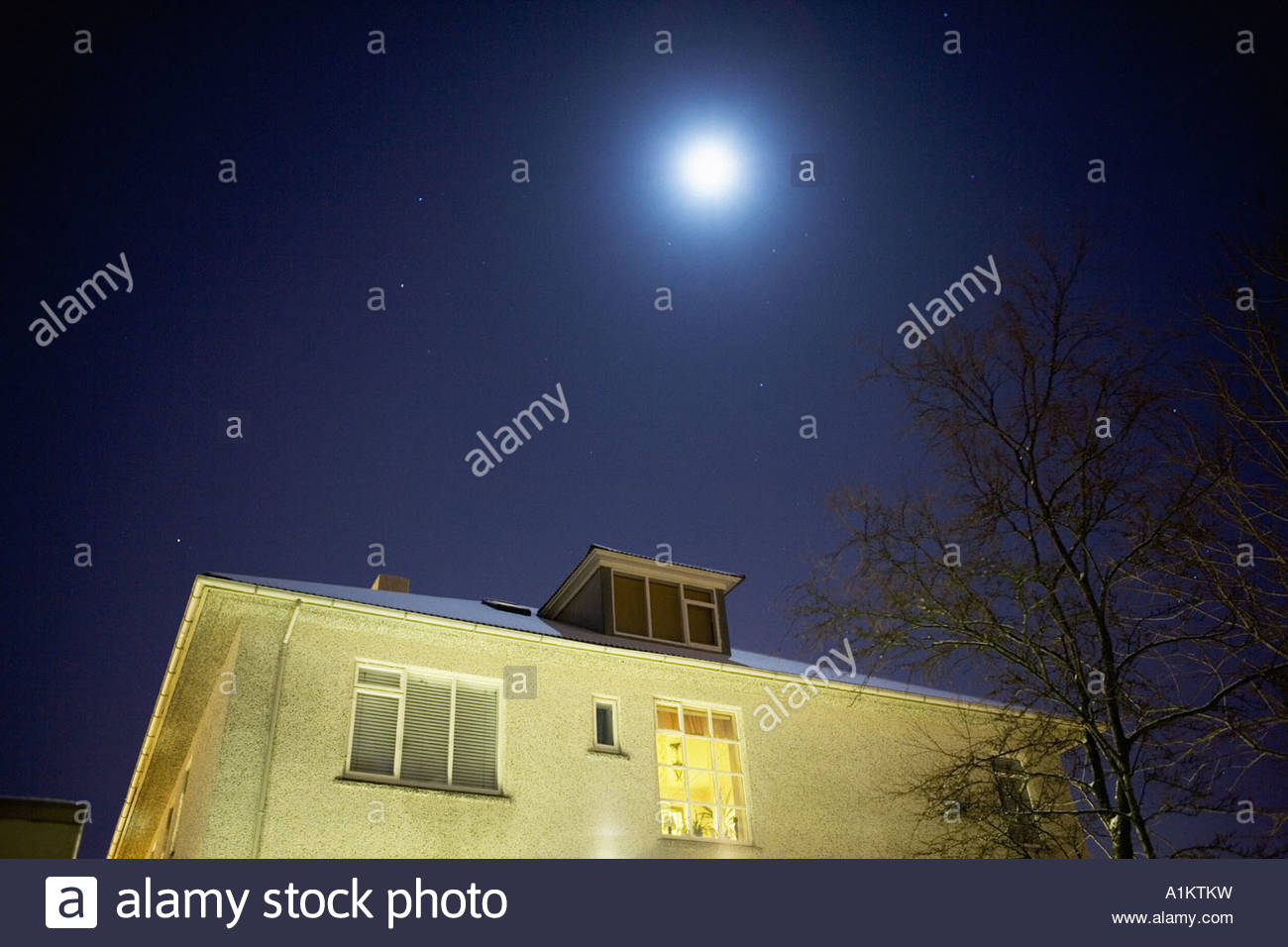Moon shining over a house in Reykjavik Iceland - Stock Image