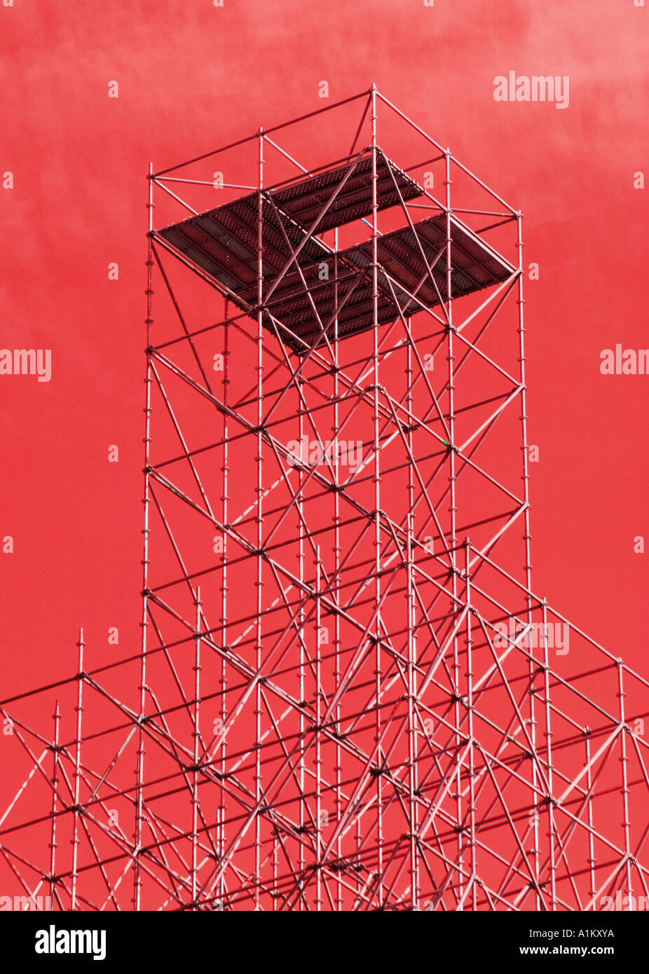 Scaffolding tower against abstracted red sky - Stock Image