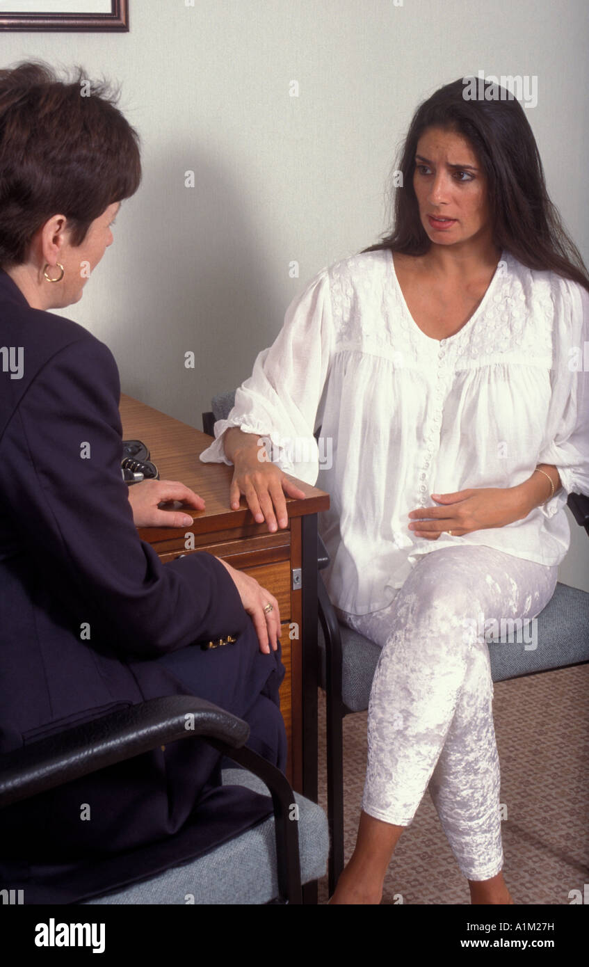 Heavily pregnant Anglo-Asian woman consulting with doctor/consultant/counsellor - Stock Image
