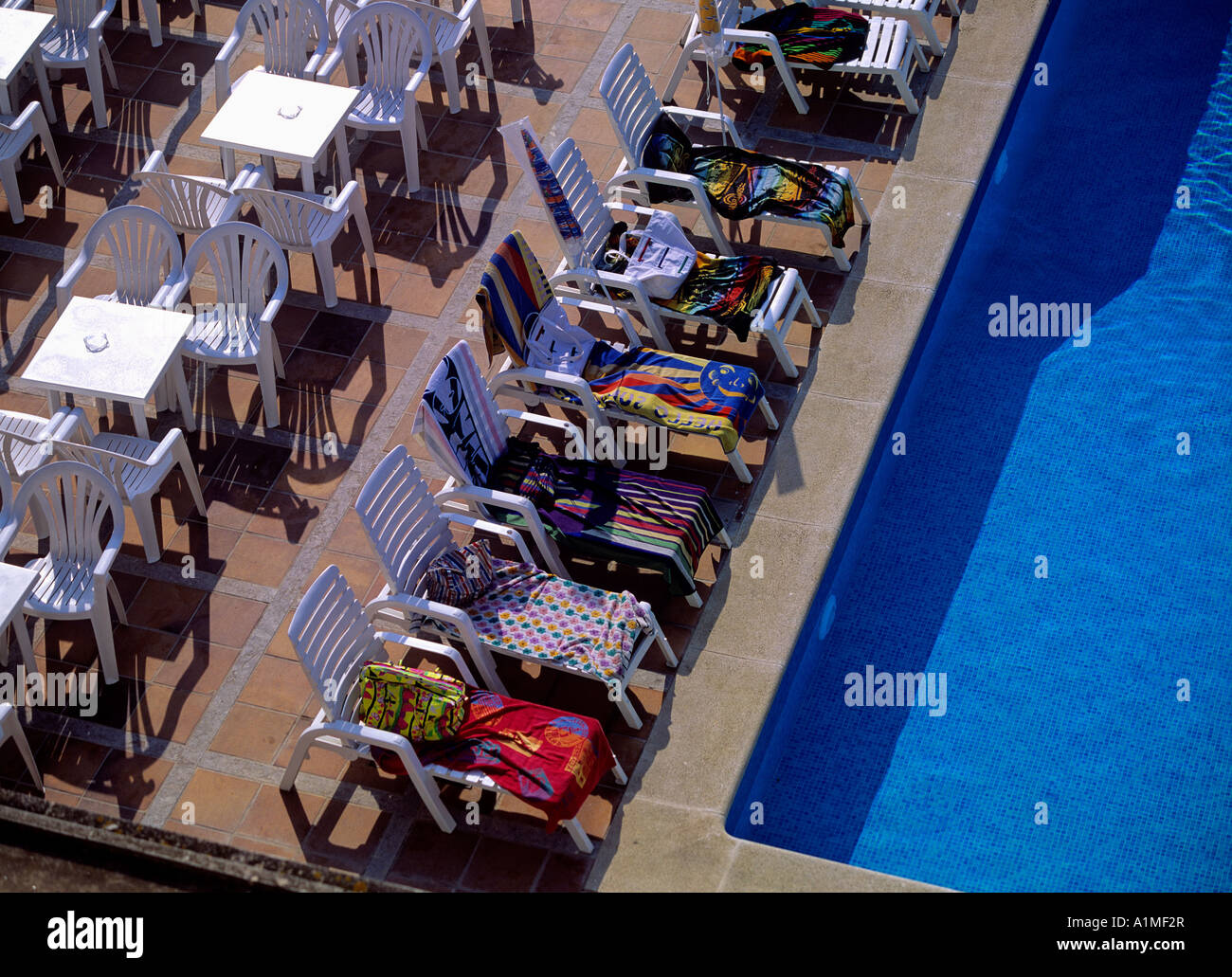 loungers at hotel swimmingpool reserved in advance - Stock Image