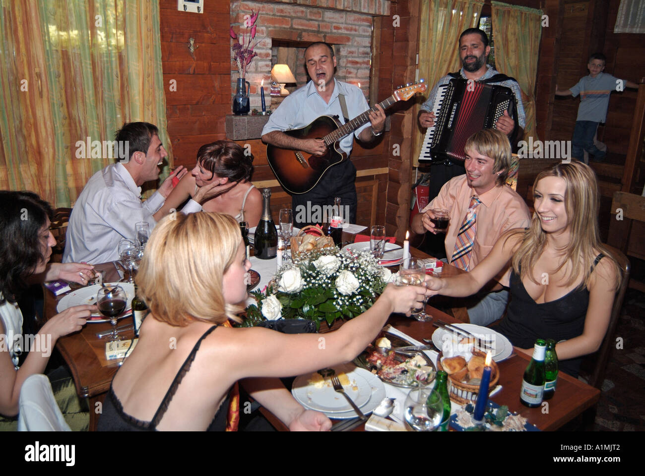 Family and Guests Celebrate an Orthodox Wedding with Traditional Folk Music and Food - Stock Image