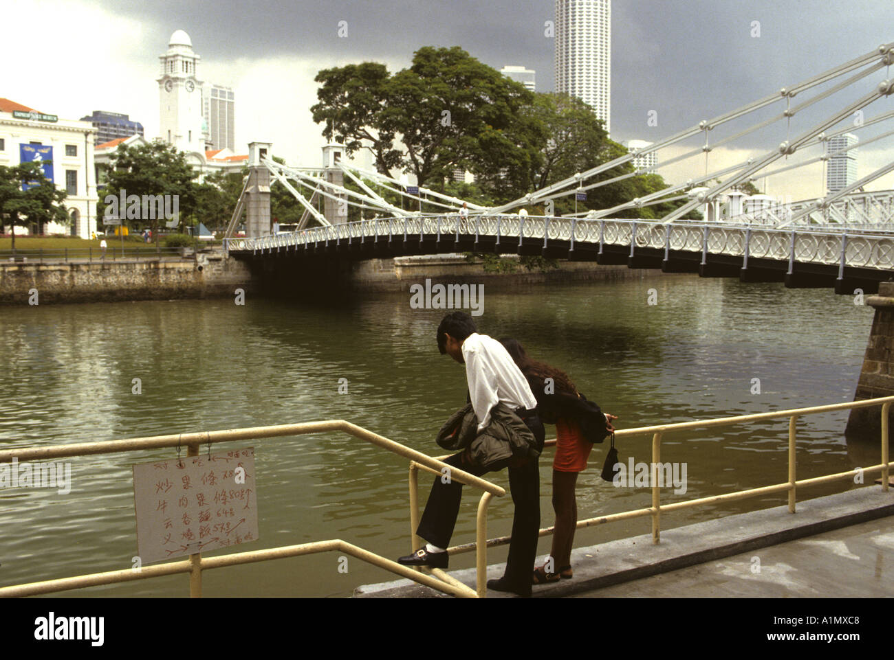 YOUNG COUPLE GAZE AT THE RIVER BY A BRIDGE IN SINGAPORE - Stock Image