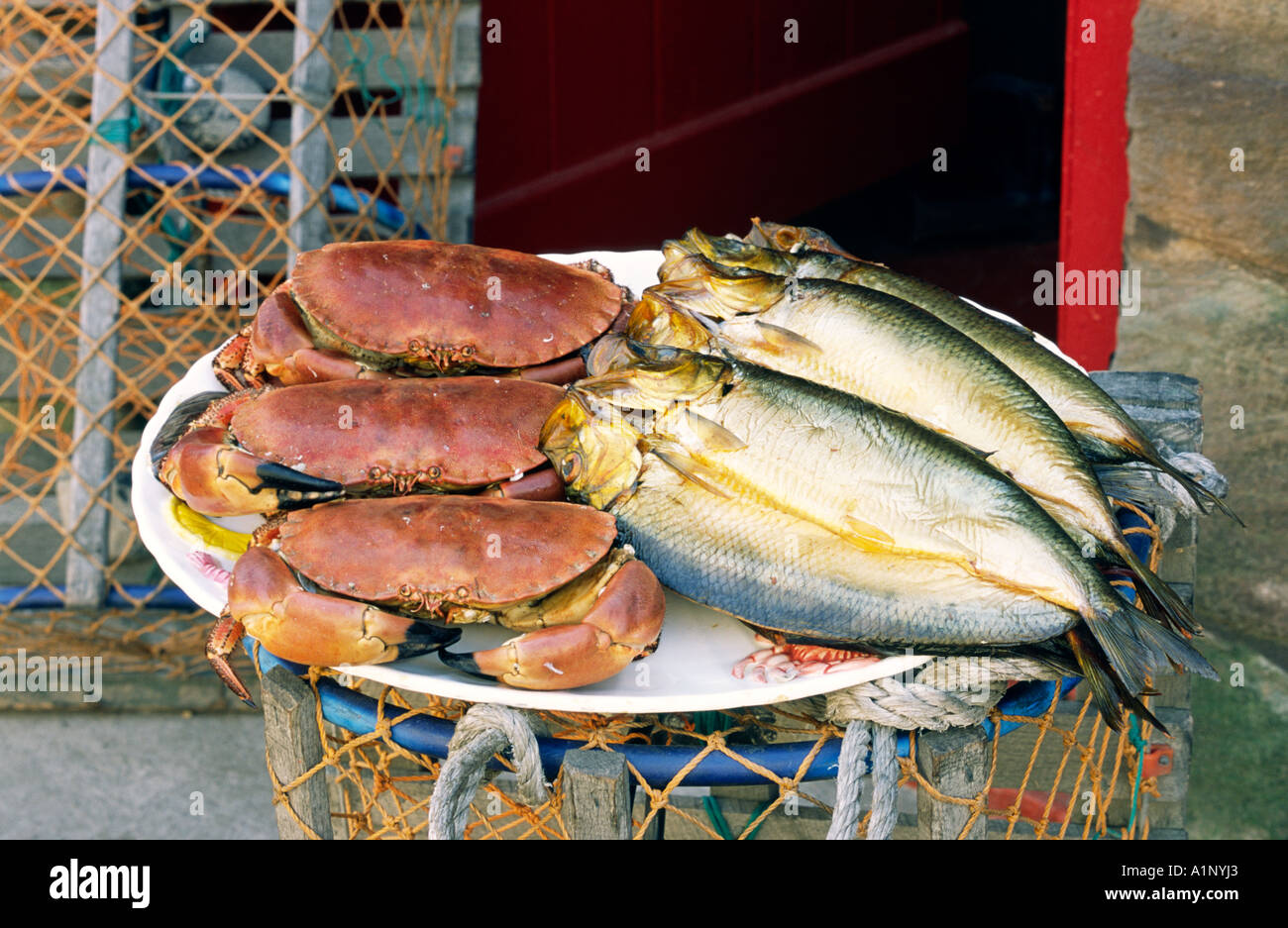Fresh kippers and crab outside the Swallowfish smokehouse shop at Seahouses, Northumberland. - Stock Image