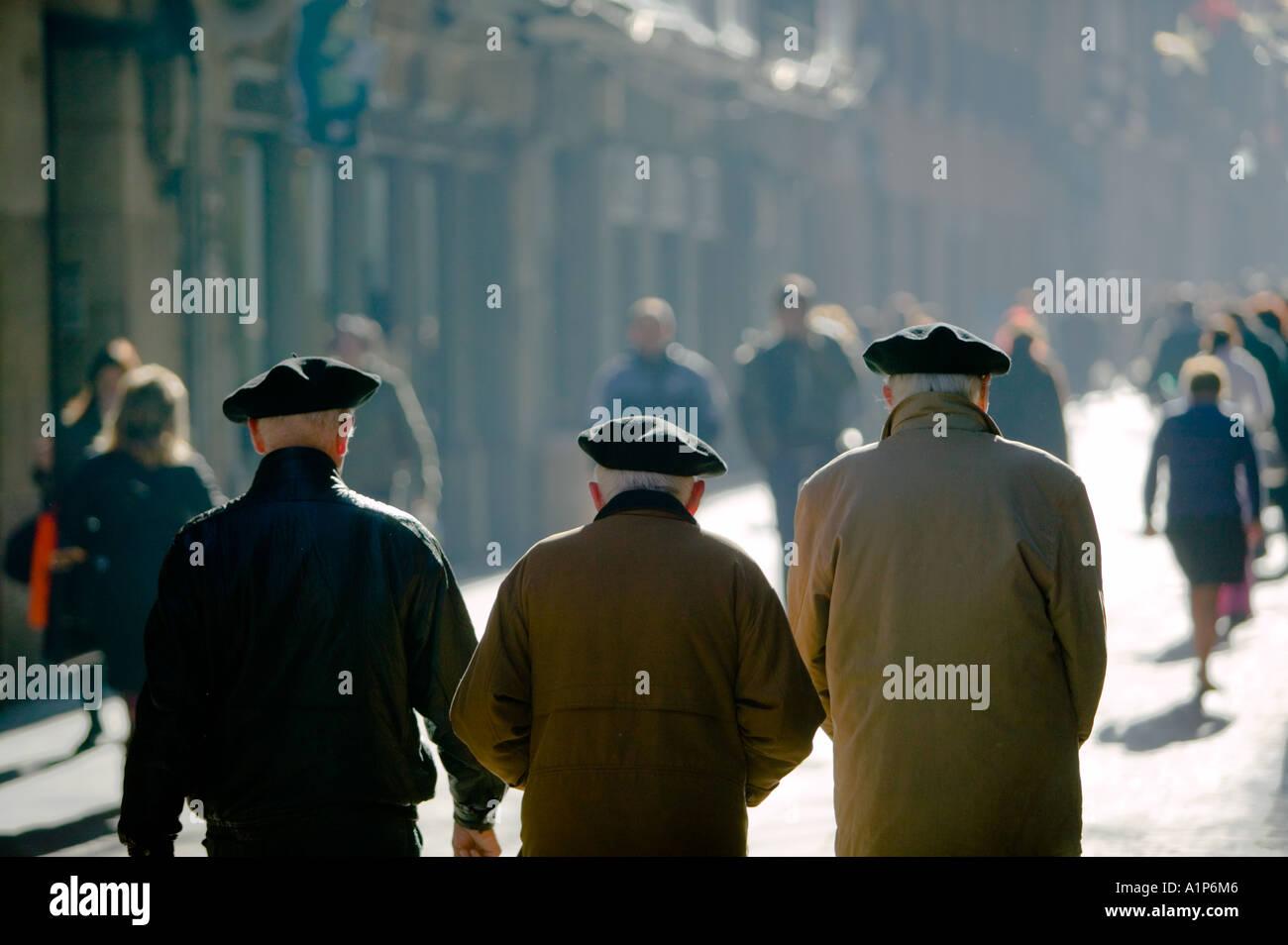 Three elderly gentlemen wearing black Basque berets walking in the sunshine, Casco Viejo, Bilbao, Pais Vasco, Spain. - Stock Image
