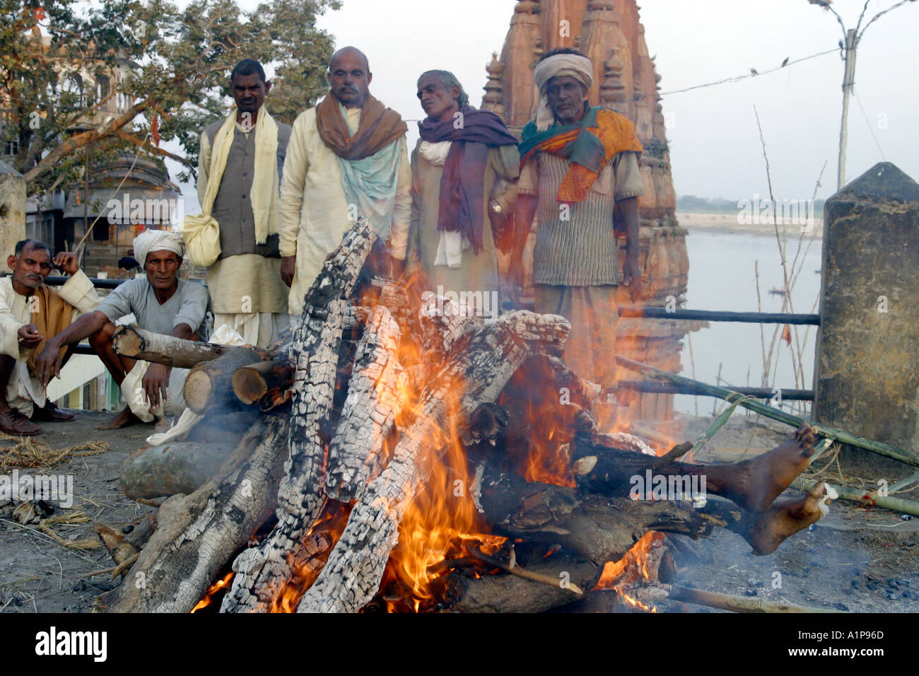 A dead body is being cremated on the banks of the holy river Ganges in Varanasi in northern India - Stock Image