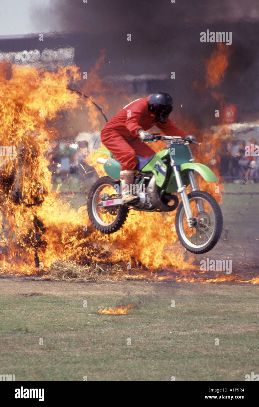Stunt rider on motorcycle driving through burning tunnel made from straw bales soaked in petrol - Stock Image