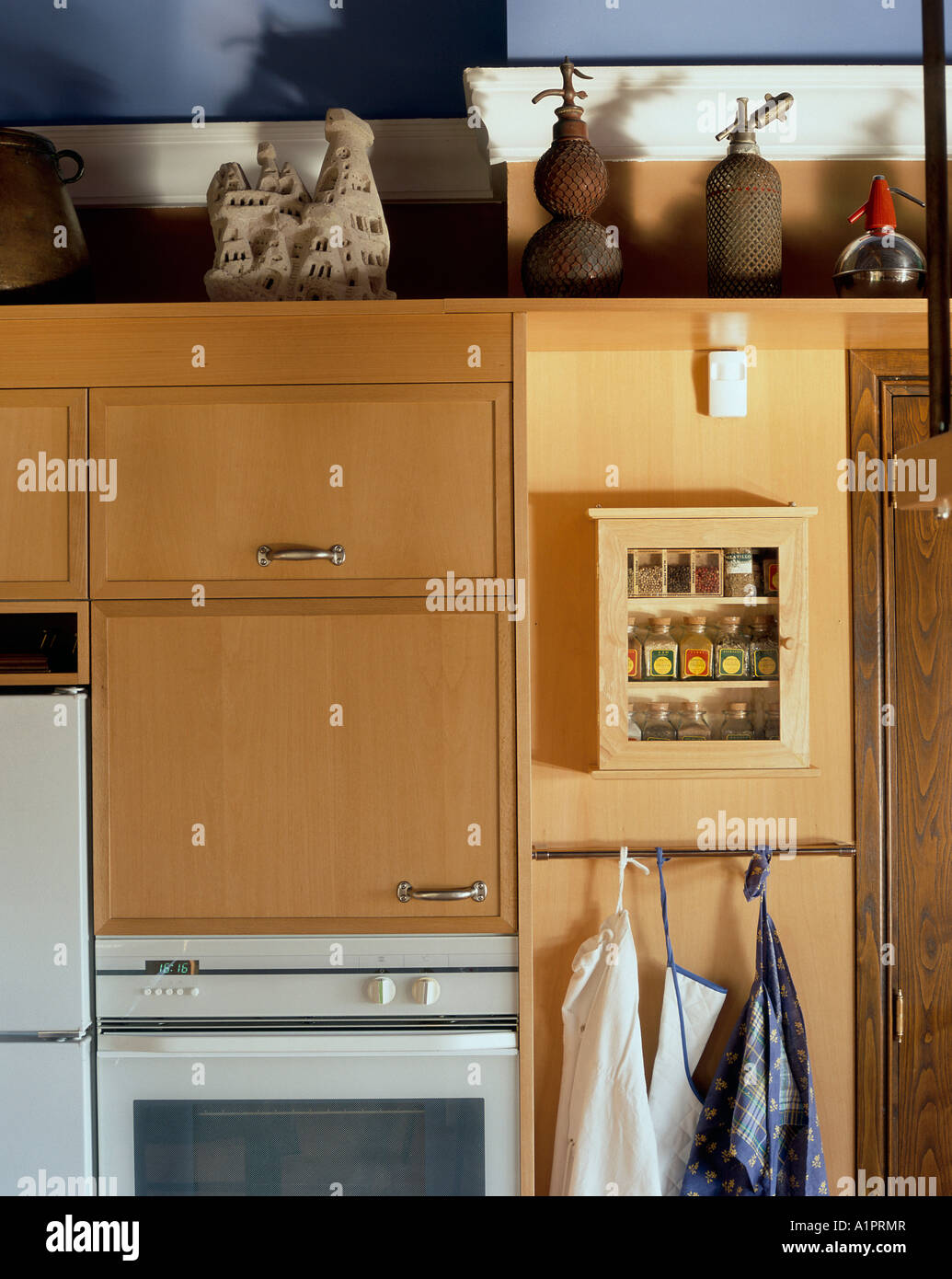 View of aprons hung near a cabinet in a kitchen - Stock Image