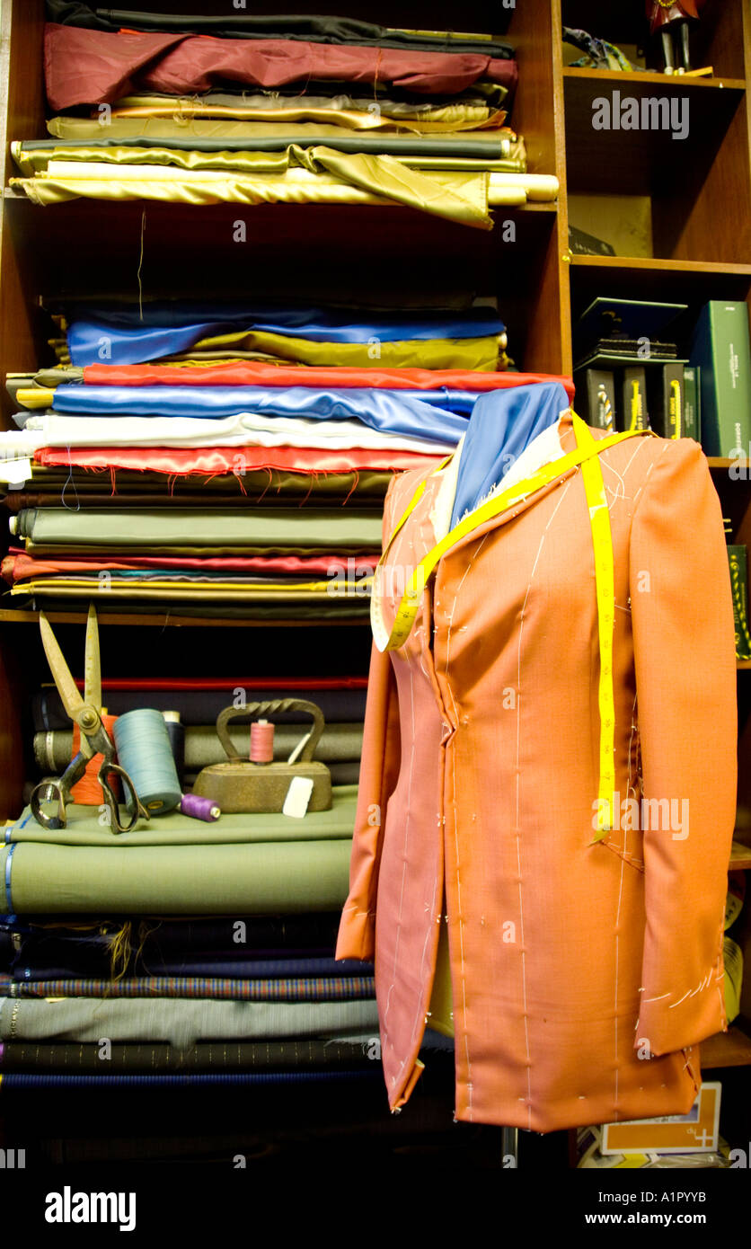 A headless mannequin on display wearing a pink blazer jacket with a yellow measuring tape hanging around the shoulders. - Stock Image