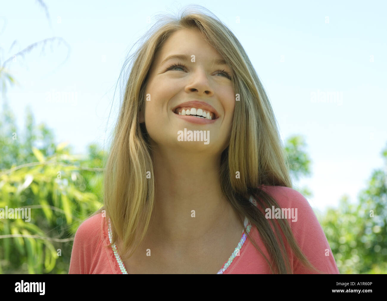 Young woman outdoors, smiling and looking up - Stock Image