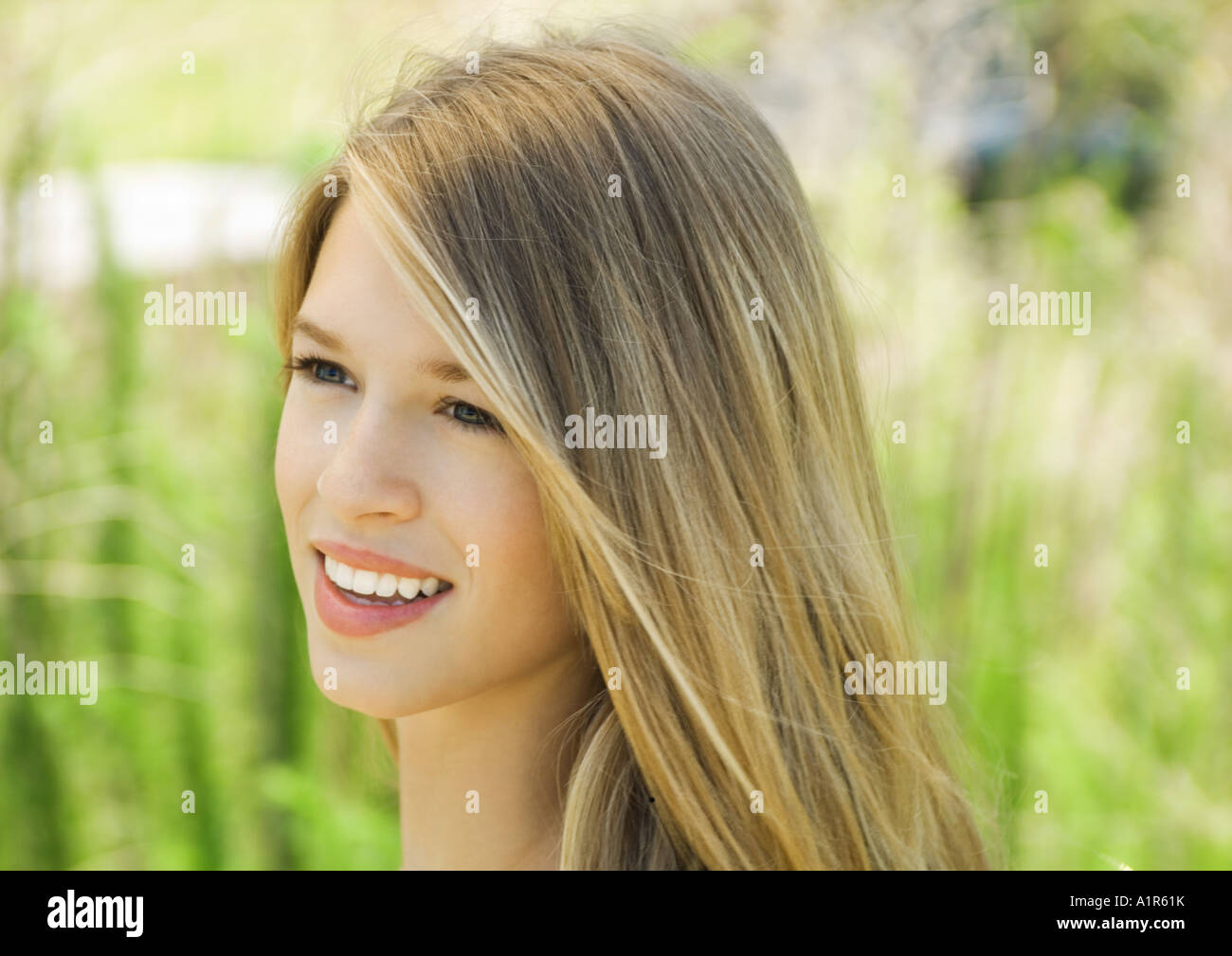 Young woman smiling outdoors, portrait - Stock Image
