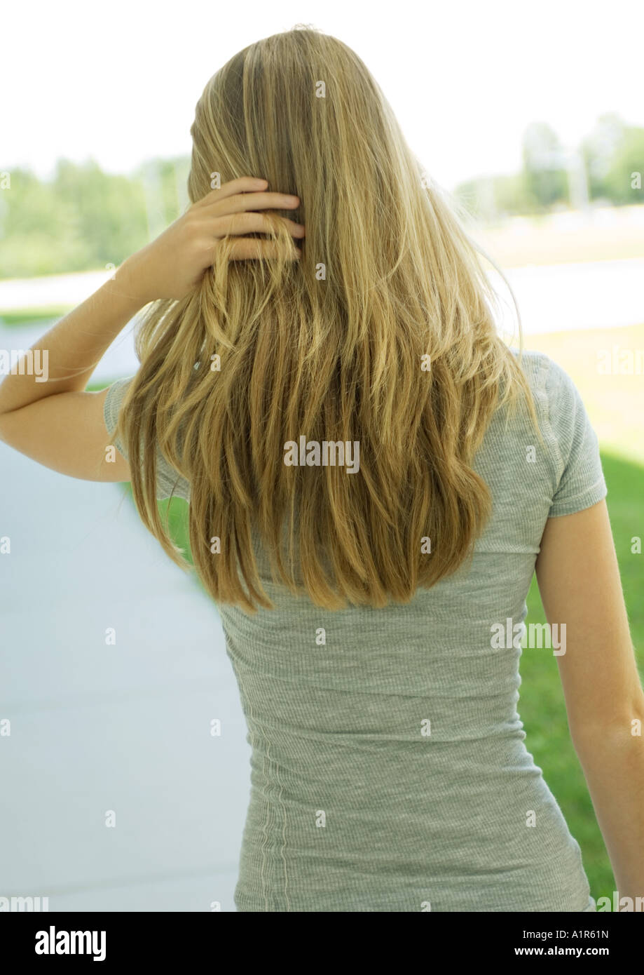Young woman pushing hair back, rear view, waist up - Stock Image