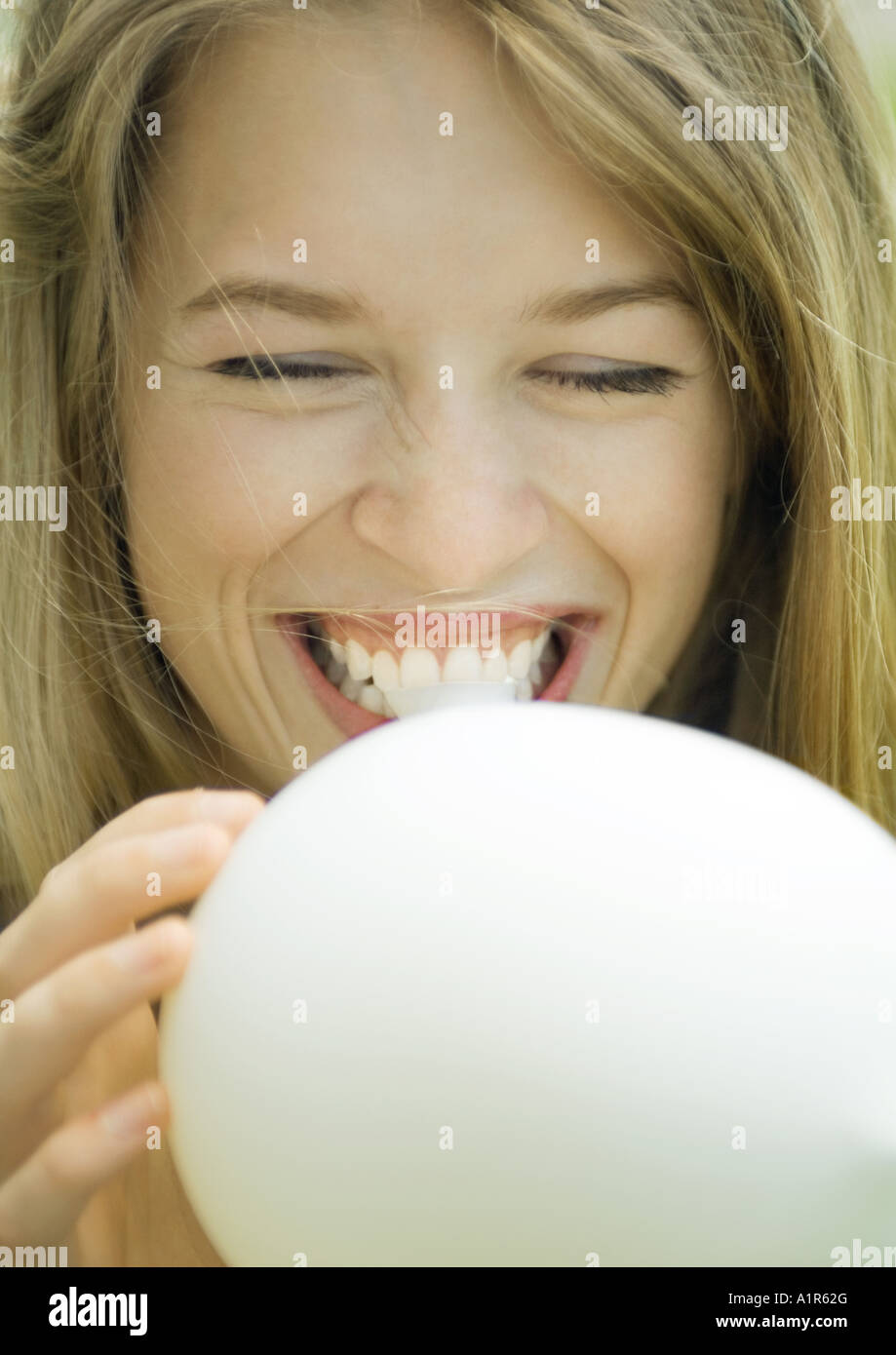 Young woman blowing up balloon, laughing, close-up - Stock Image