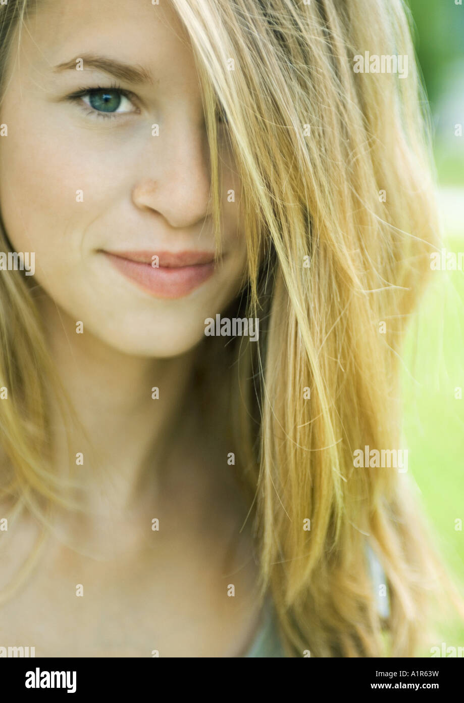 Young woman smiling, hair covering one eye, looking at camera, portrait - Stock Image