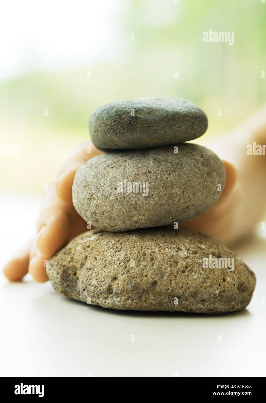 Hand touching stack of pebbles - Stock Image