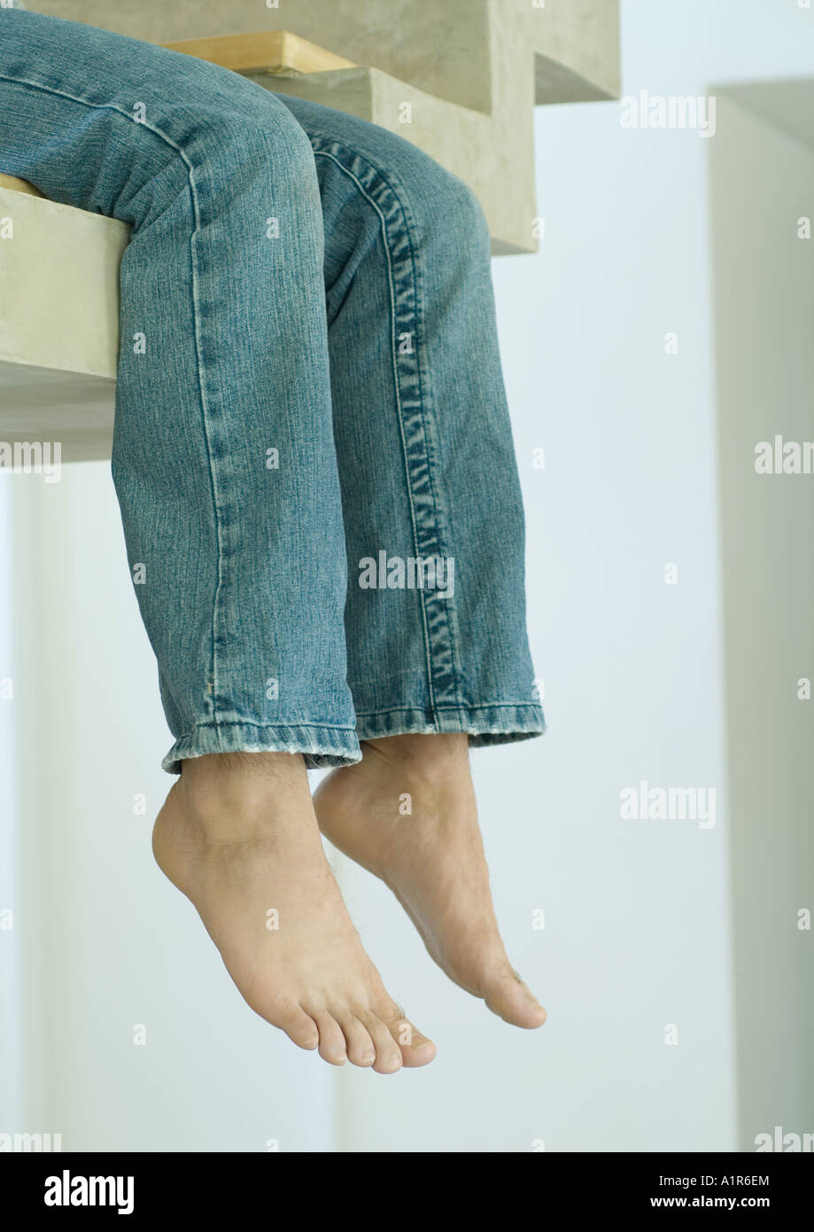 Man sitting on edge of staircase, legs dangling, low section - Stock Image