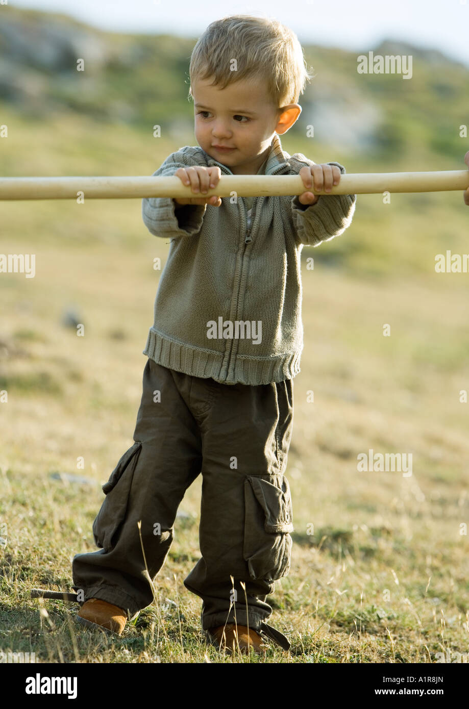 Child holding on to wooden stick - Stock Image