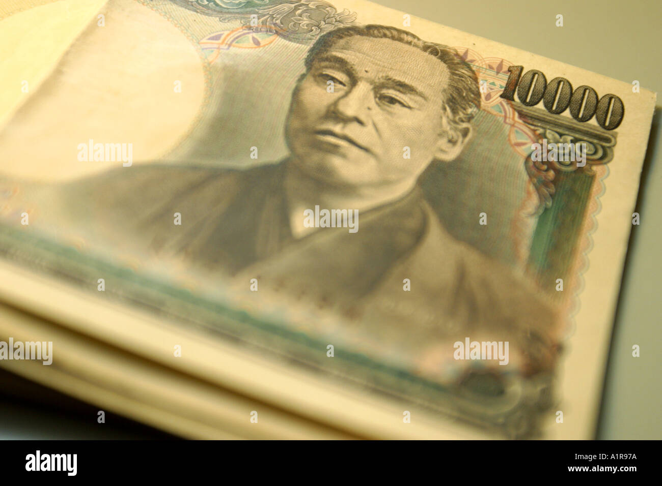 Japanese coins on dollar notes blurred - Stock Image