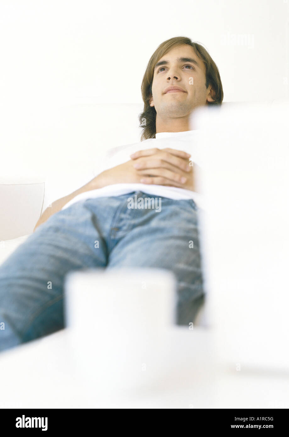 Man lying down, looking up - Stock Image