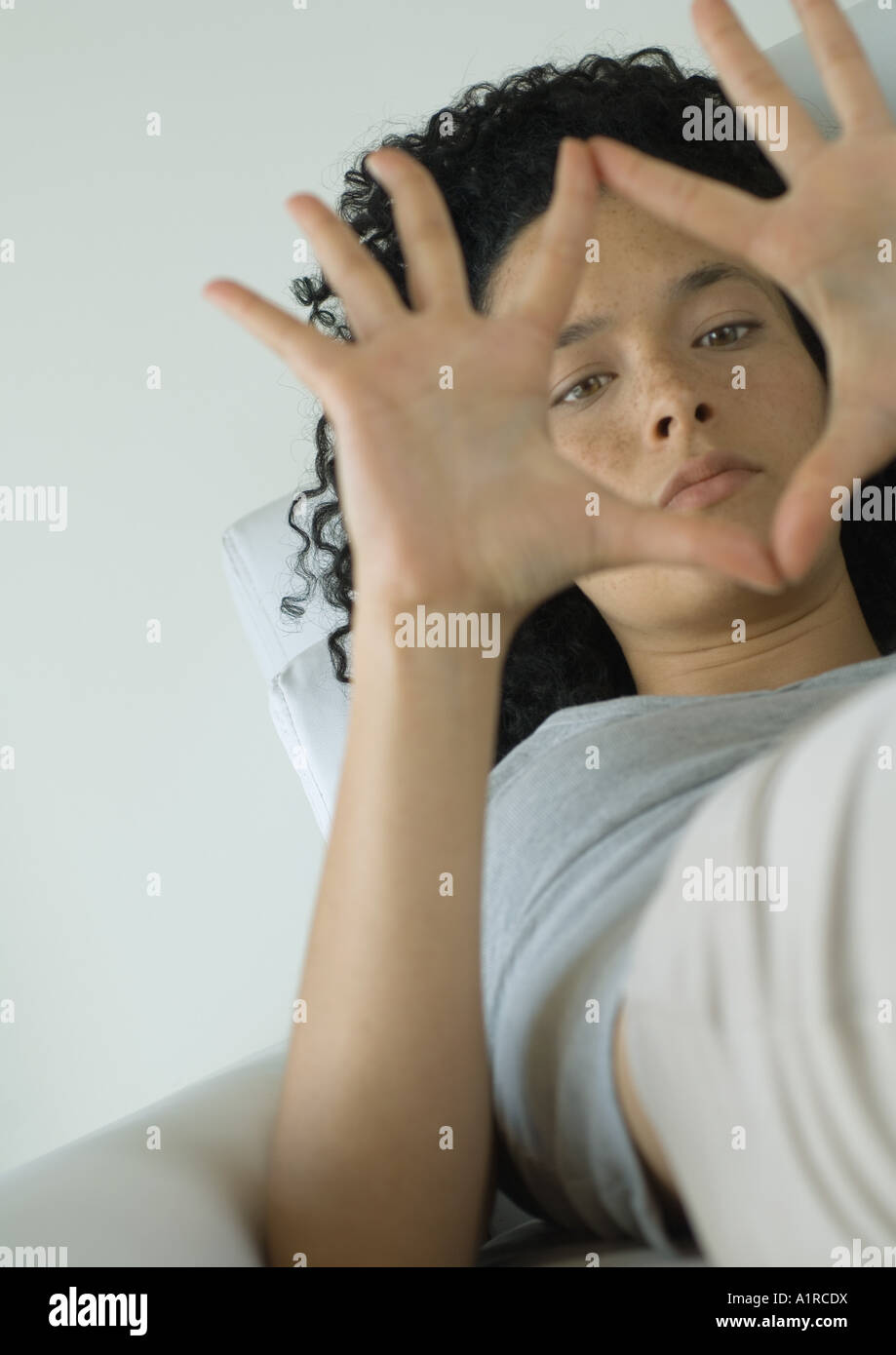 Woman lying down, making frame with hands - Stock Image