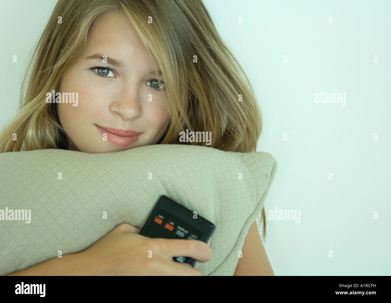Woman holding cushion and remote control - Stock Image