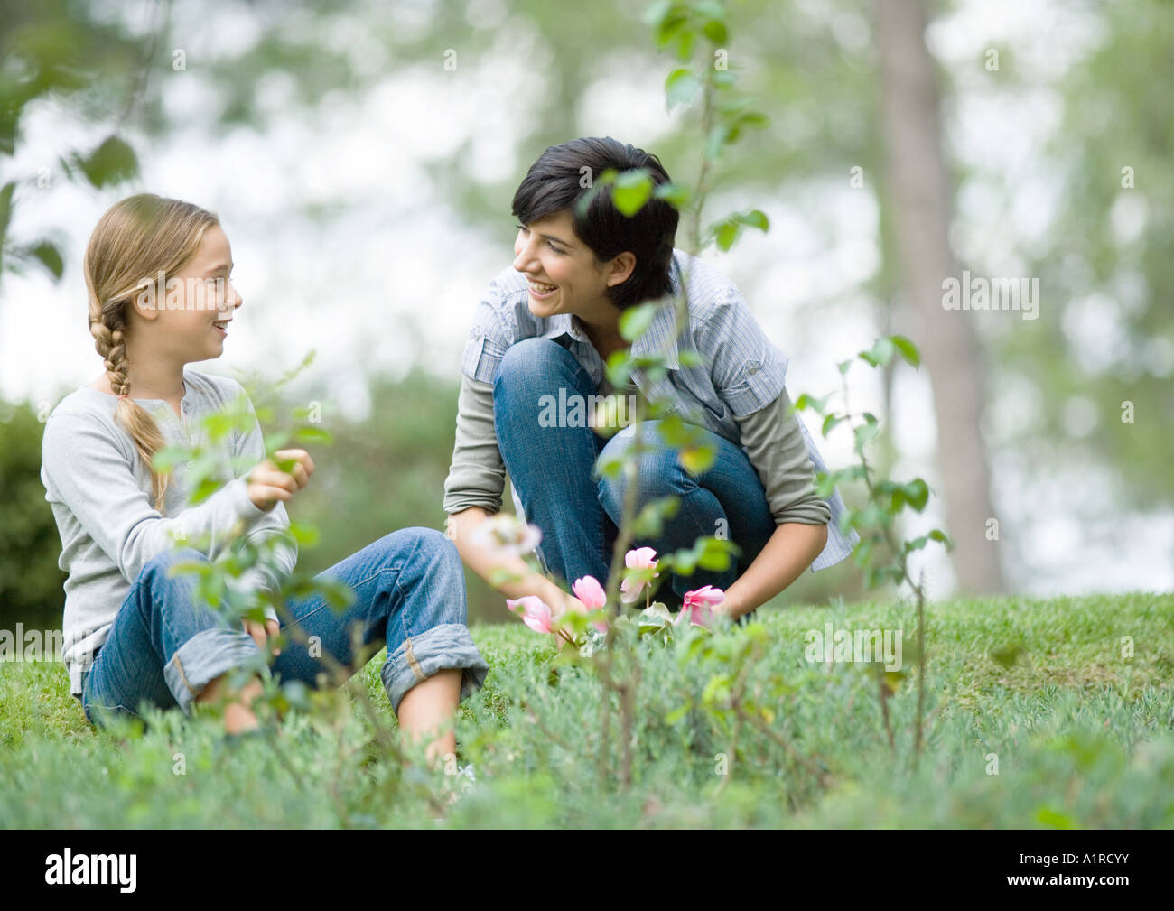 Mother and daughter doing yardwork, chatting - Stock Image