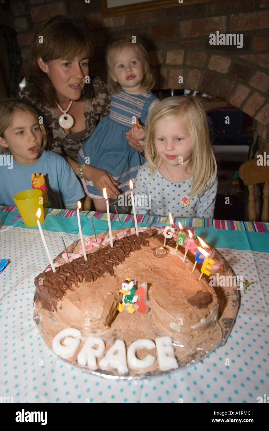 Four Year Old Girl Blowing Out Candles On Chocolate Birthday Cake UK