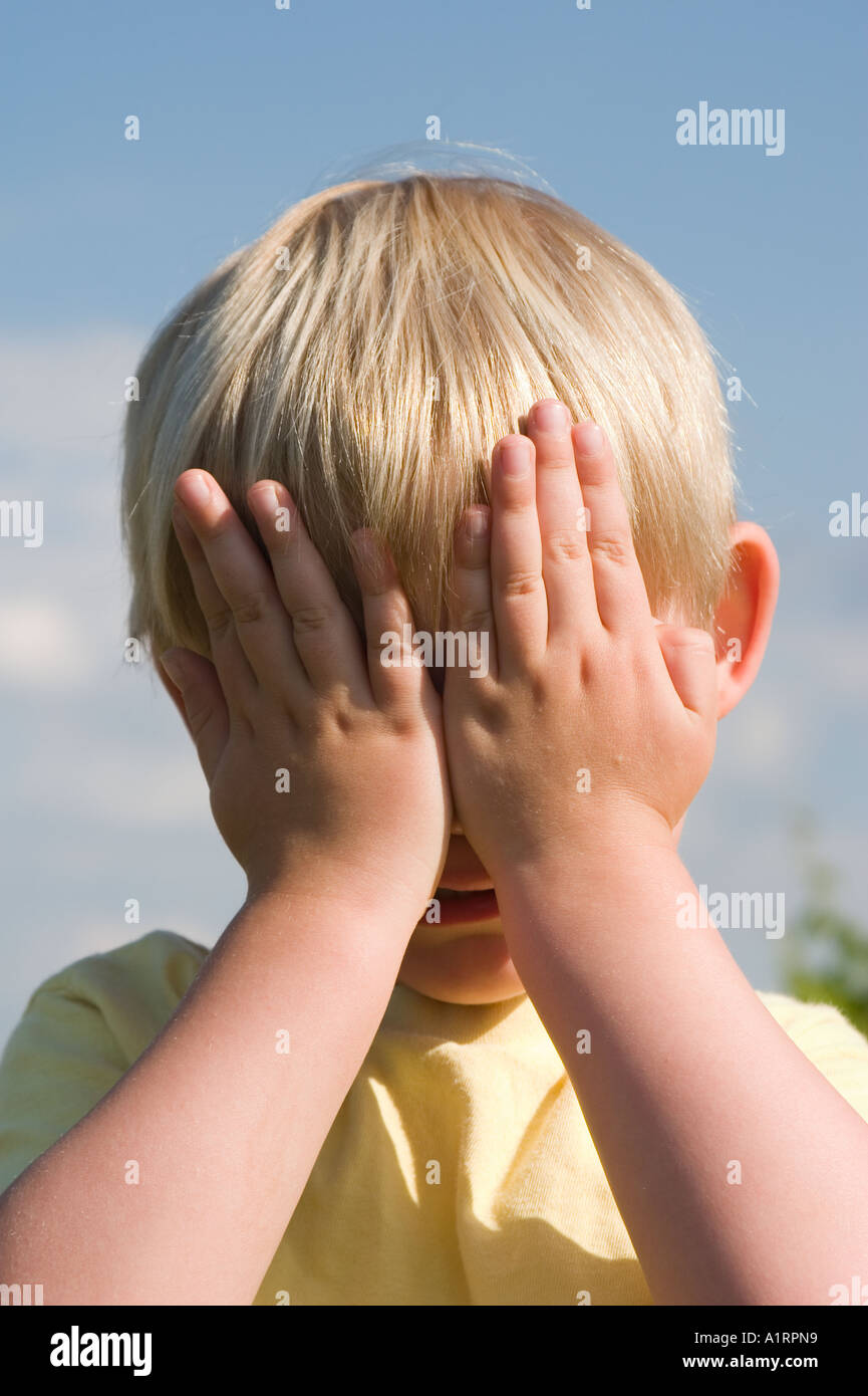 little boy holding hands in front of his eyes holding his eyes shut - Stock Image
