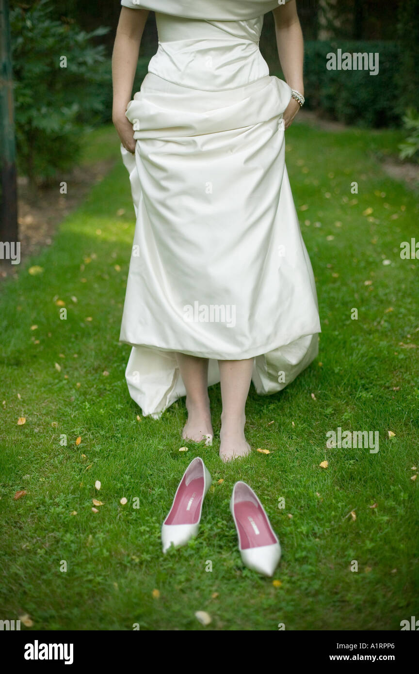 Wedding bride with aching feet because of her shoes - Stock Image