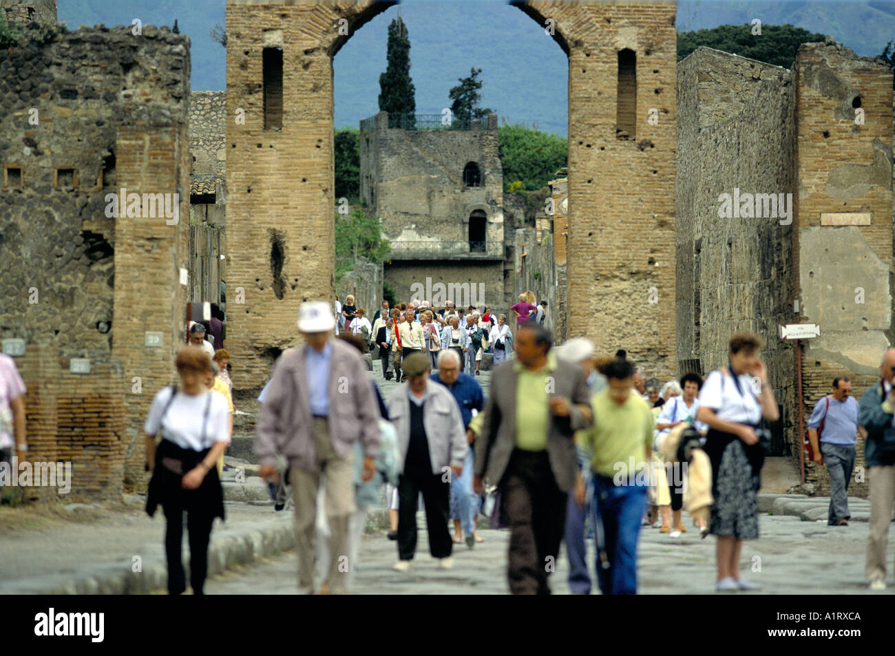 TOUIRISTS WALKING THROUGH ARCHWAY WHILE VISITING THE ANCIENT ROMAN RUINS AT POMPEI Stock Photo