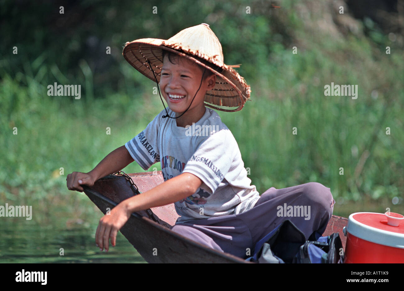 Portrait of a Vietnamese boy in a palm hat on the prow of a sampan Perfume Pagoda river route near Hanoi Vietnam - Stock Image