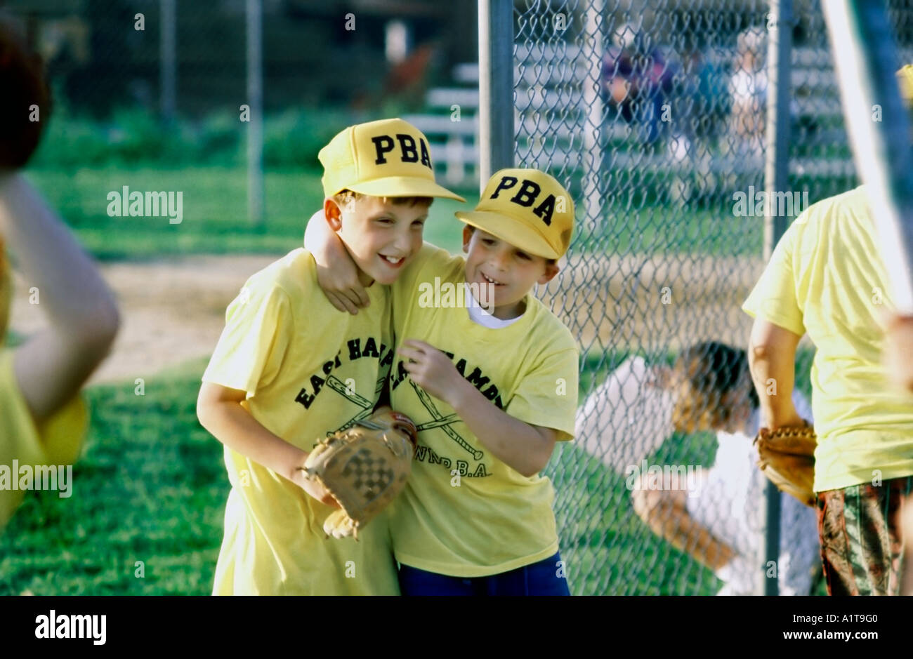 EAST HAMPTON NY USA Two 'Young Teens' Hugging at Male 'Baseball Game''Children Playing' 'Little League' Uniforms Sports - Stock Image