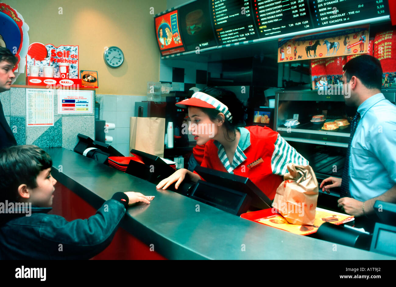 Paris France, Female French Teen Working in 'Fast Food Restaurant' Taking order From Boy  at Counter - Stock Image