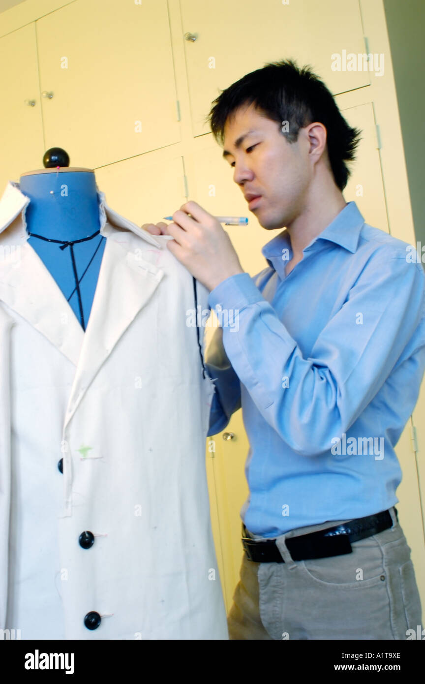 Portrait Young Asian Ethnicity Man Tailor Working on Suit with Dummy in Studio Single People male student - Stock Image