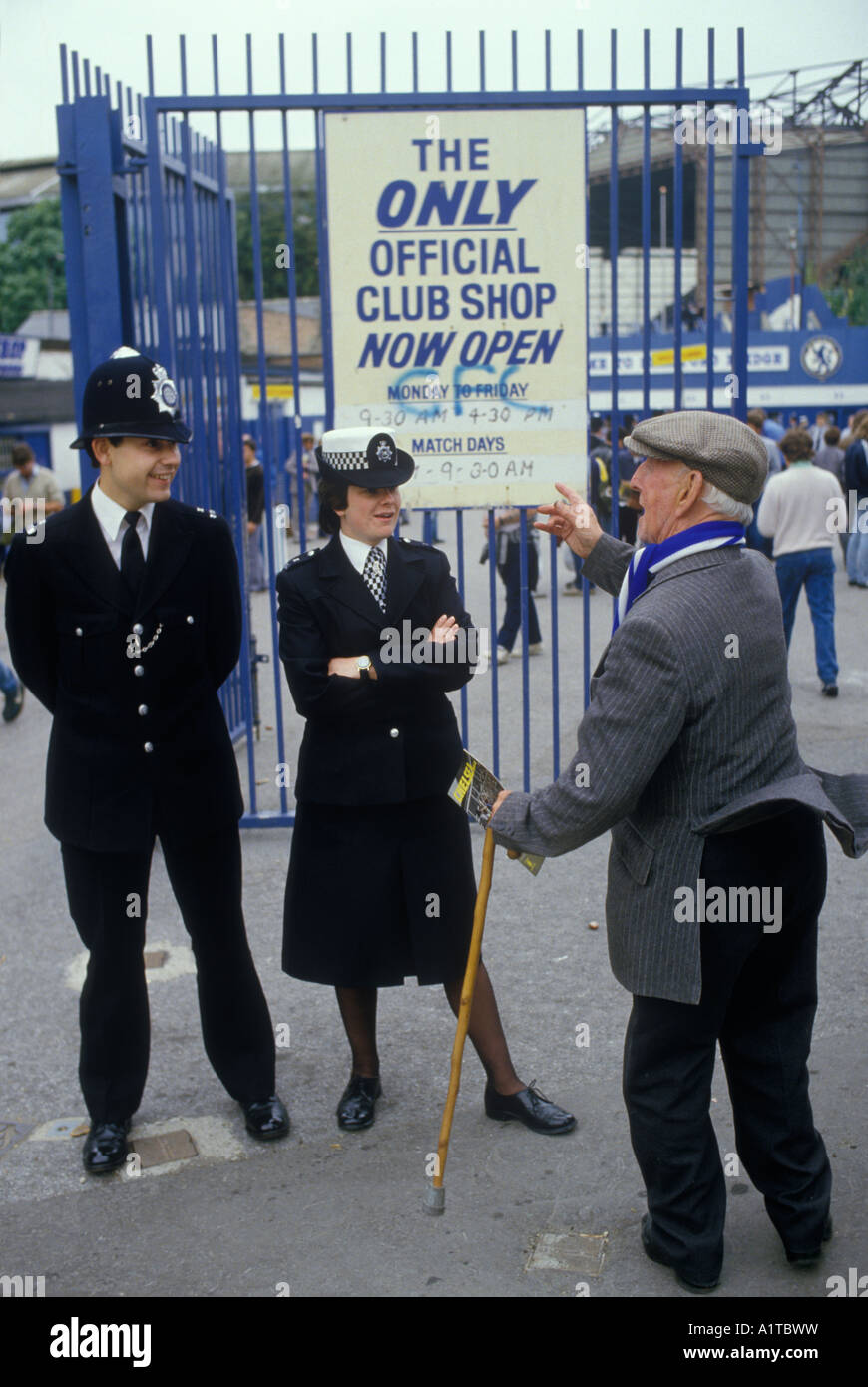 Chelsea Football fan talking a policeman and policewoman on crowd controle duty at the   Stamford Bridge London Stock Photo