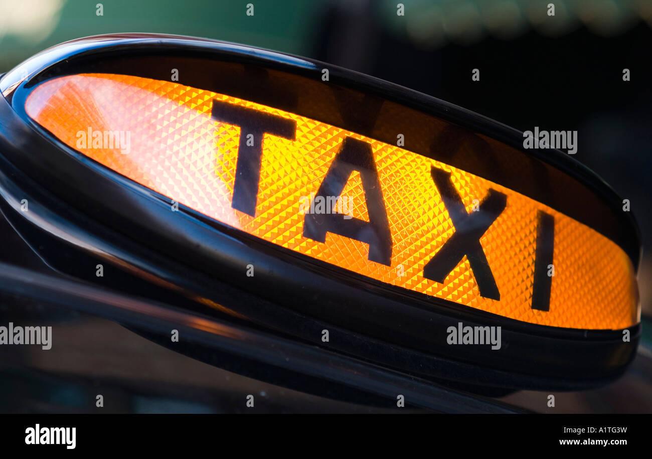 Taxi black cab sign illuminated and waiting for custom London England - Stock Image