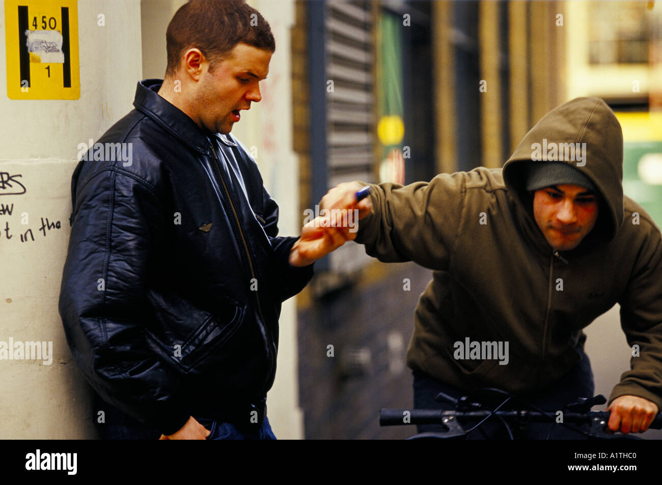 STREET CRIME MALE YOUTH ON MOUNTAIN BIKE SNATCHING MOBILE PHONE FROM SURPRISED MAN POSED BY MODELS 2002 - Stock Image