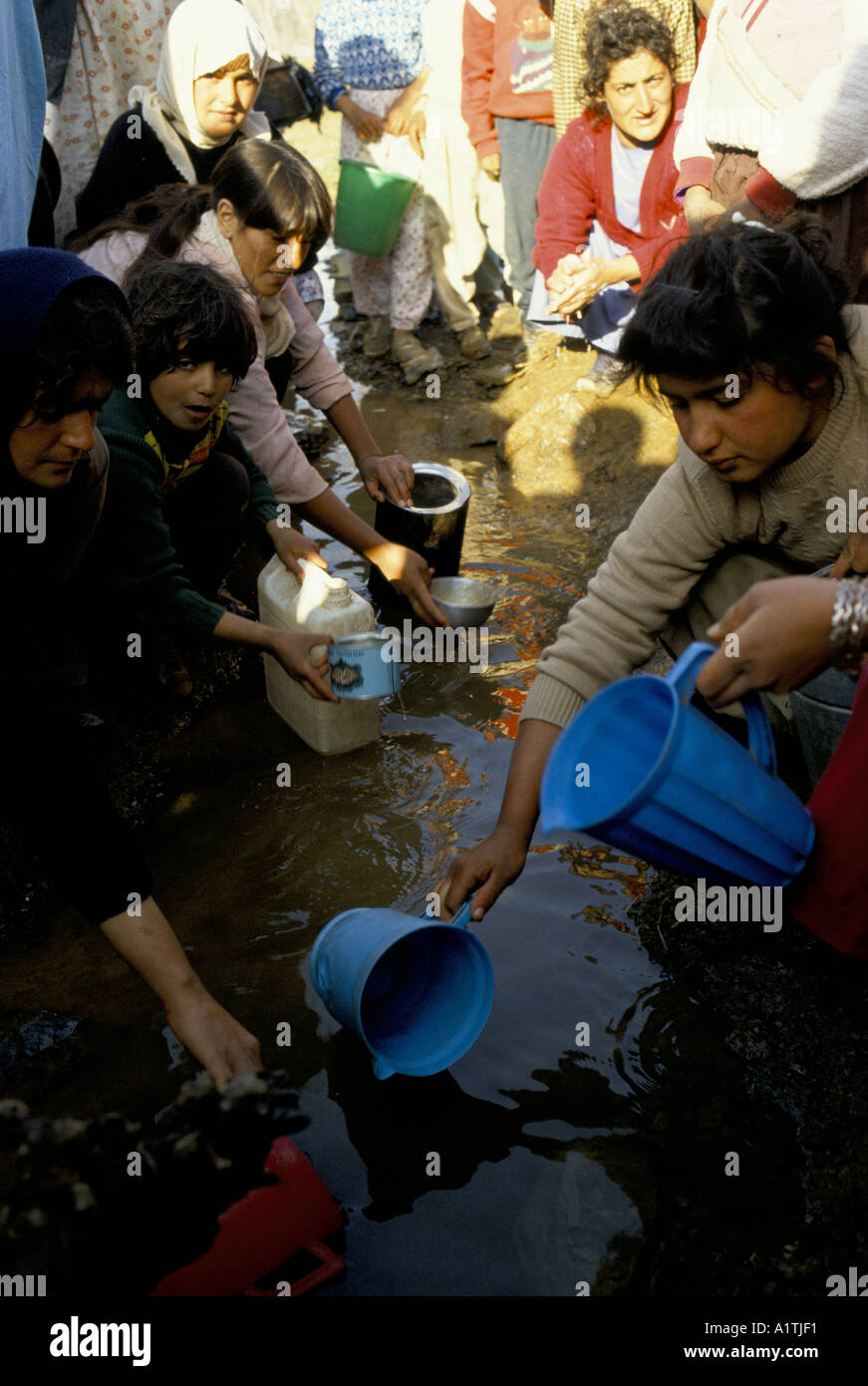 KURDISH REFUGEES ON IRAN IRAQ BORDER APRIL 1991 trying to find clean water - Stock Image