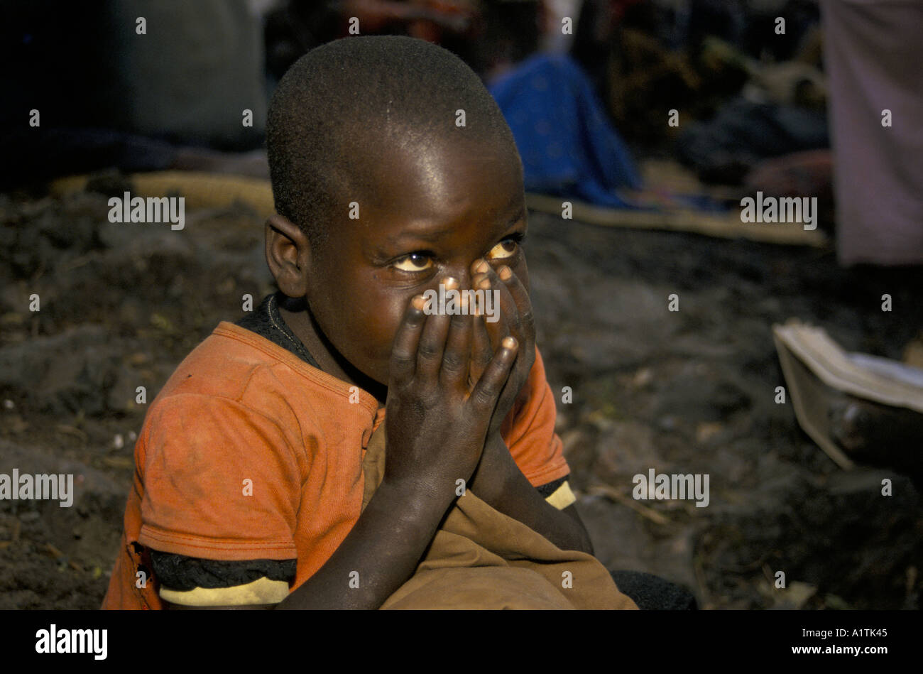 GOMA ZAIRE RWANDAN REFUGEES IN KIBUMBA REFUGEE CAMP JULY 1994,Child sitting with her hands in front of her face. - Stock Image