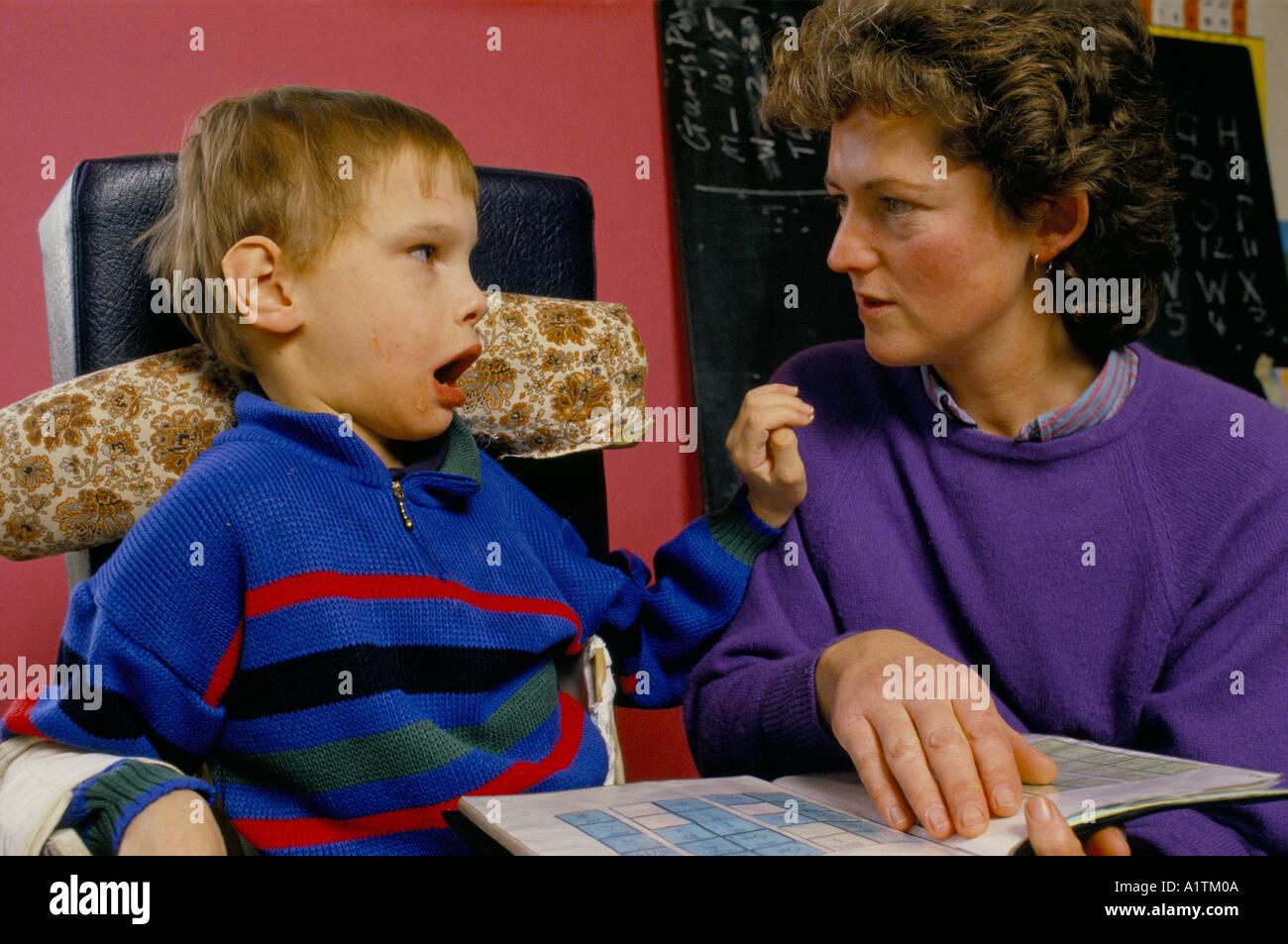 DISABLED CHILD TALKING USING BLISS SYMBOLS - Stock Image