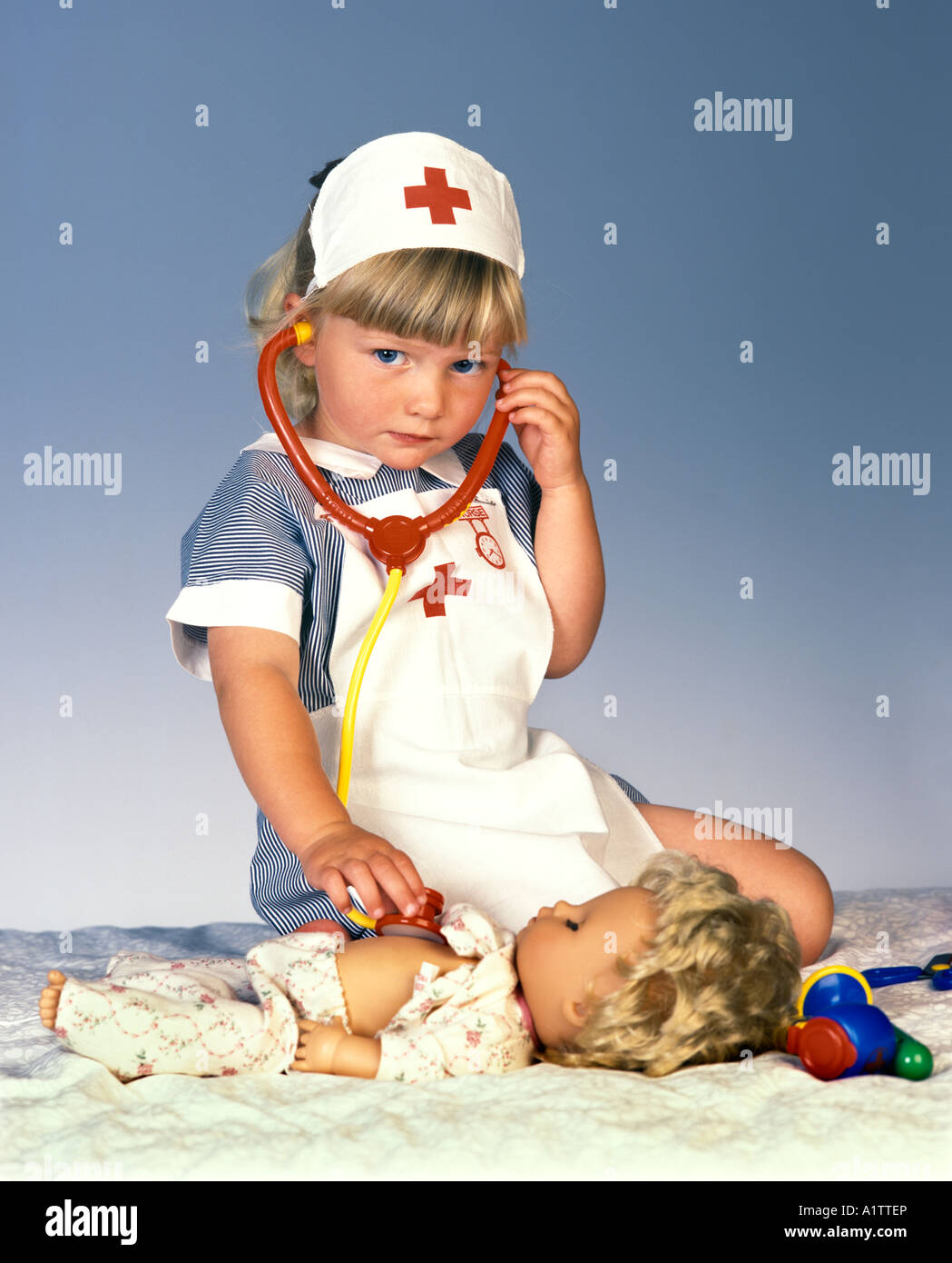 A young girl in a nurses costume plays with her doll and a stethoscope Stock Photo