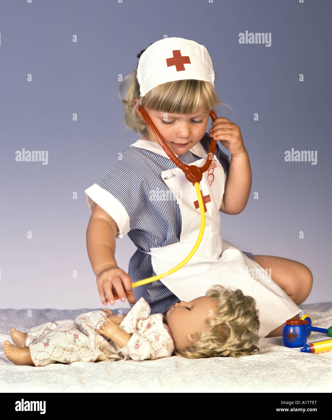 7bd2e2be30f87 A young girl in a nurses costume plays with her doll and a stethoscope