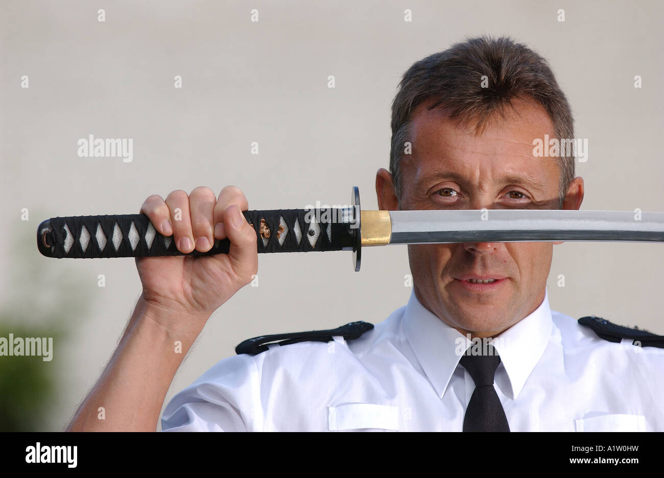 A policeman holding a samurai sword Stock Photo