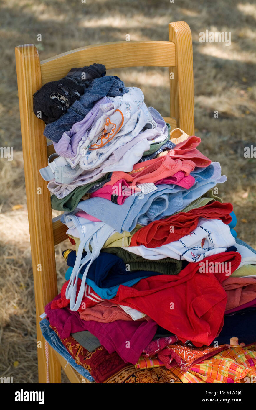 Stack of laundry on a chair in the backyard / garden. - Stock Image