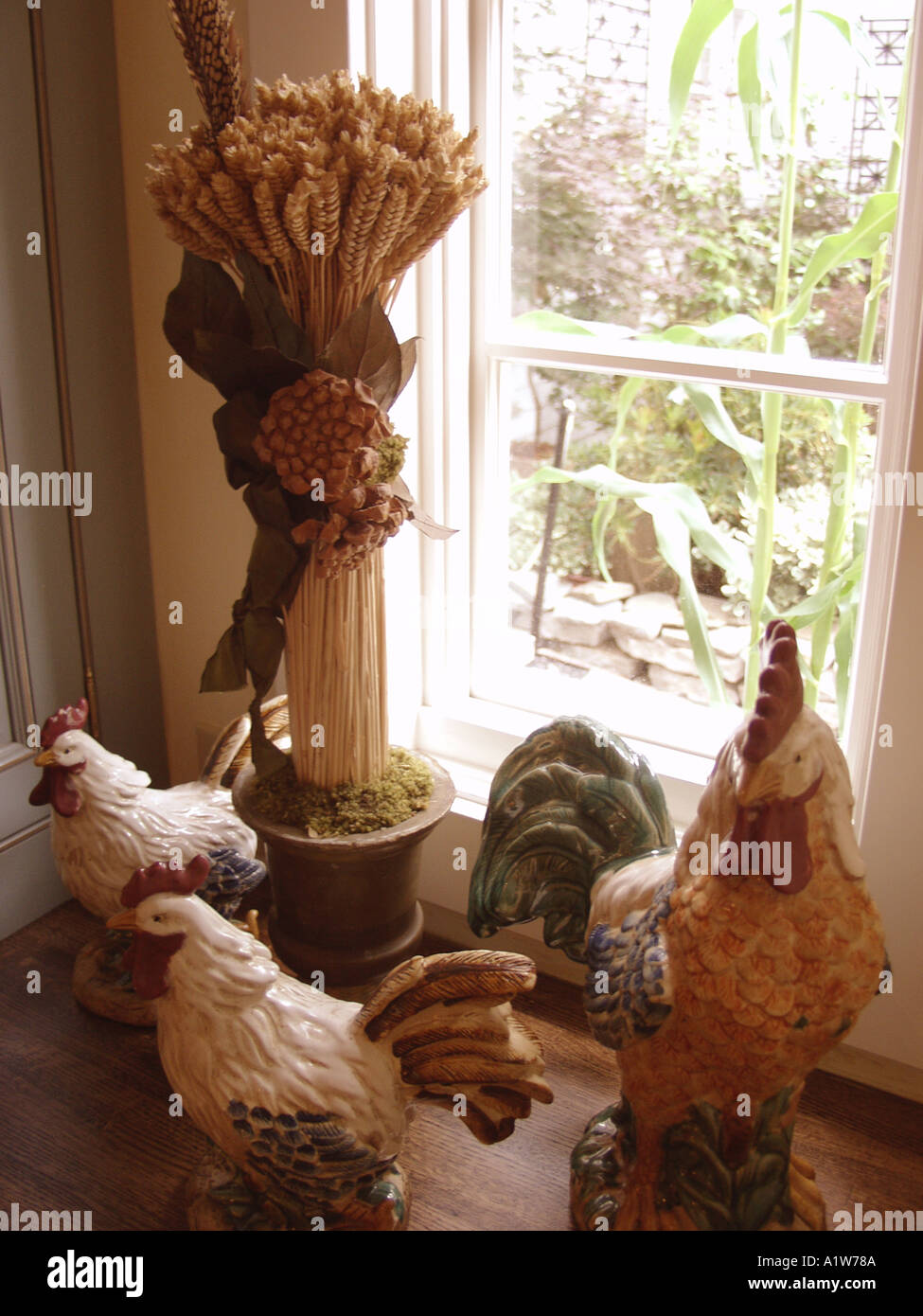 decorative wheat in vase on window sill - Stock Image
