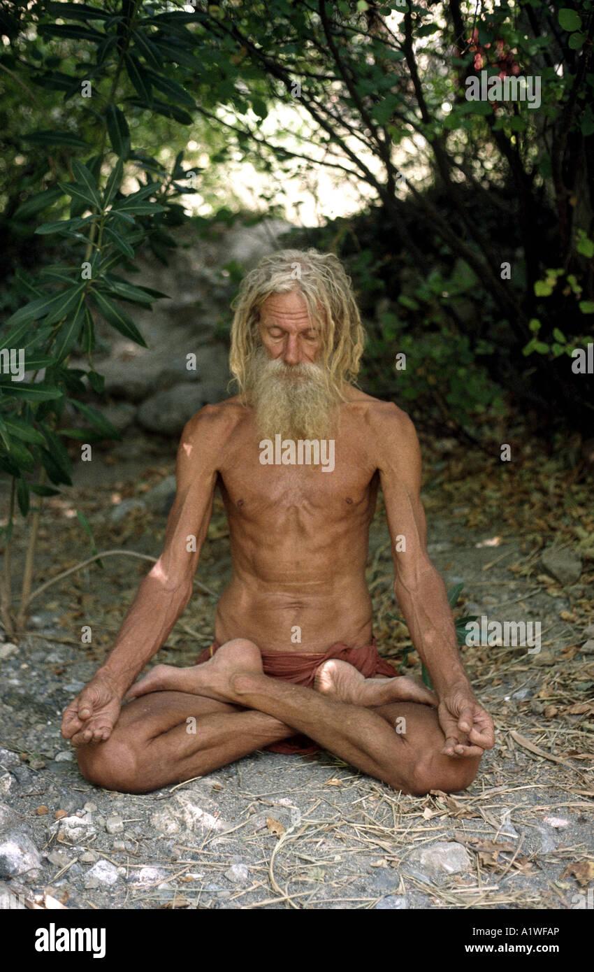 Yogi who resides in Crete meditating in full lotus yogi position - Stock Image