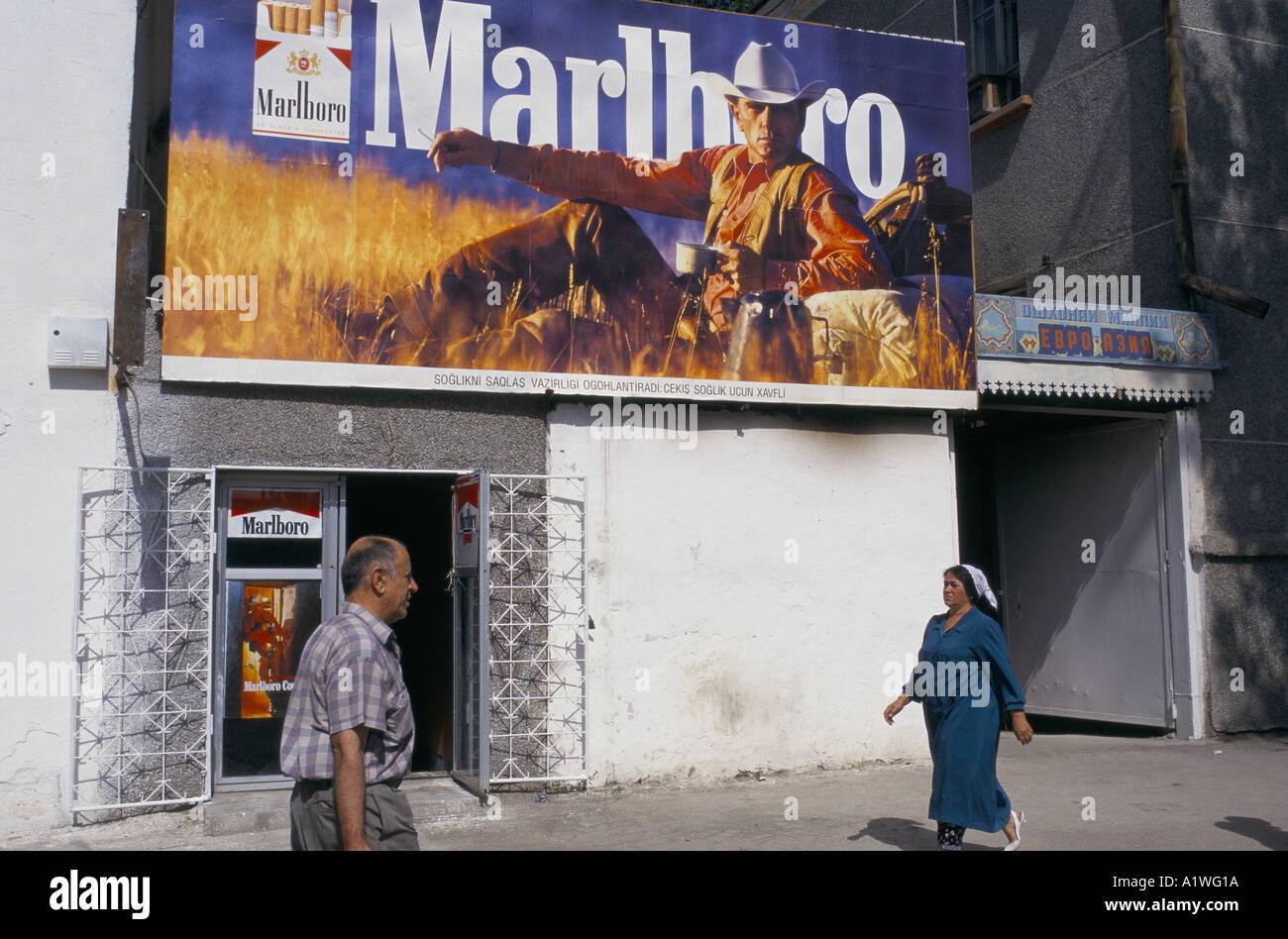 Man and women walking in front of a Marlboro advert, Tajikistan - Stock Image