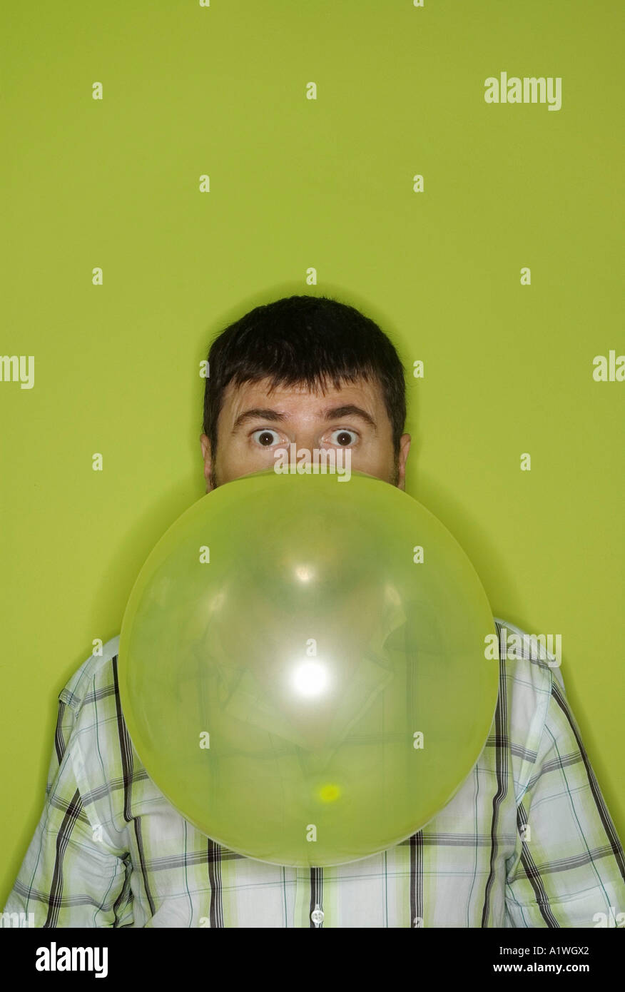 MAN INFLATING BALLOON - Stock Image