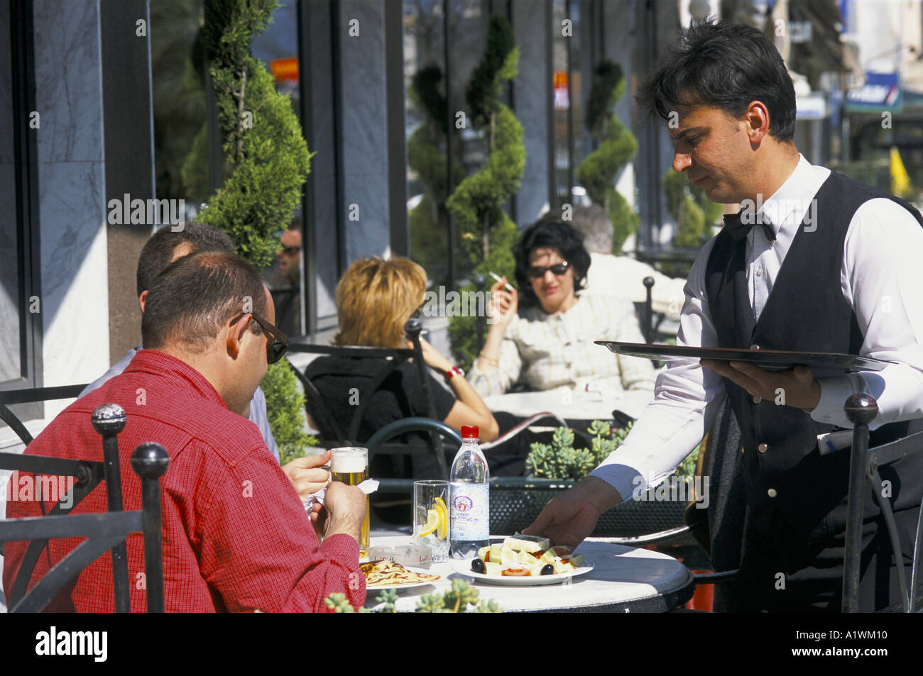 WAITER SERVING CUSTOMERS SITTING AT CAFE TABLE IN THE PIAZZA TIRANA 2001 - Stock Image