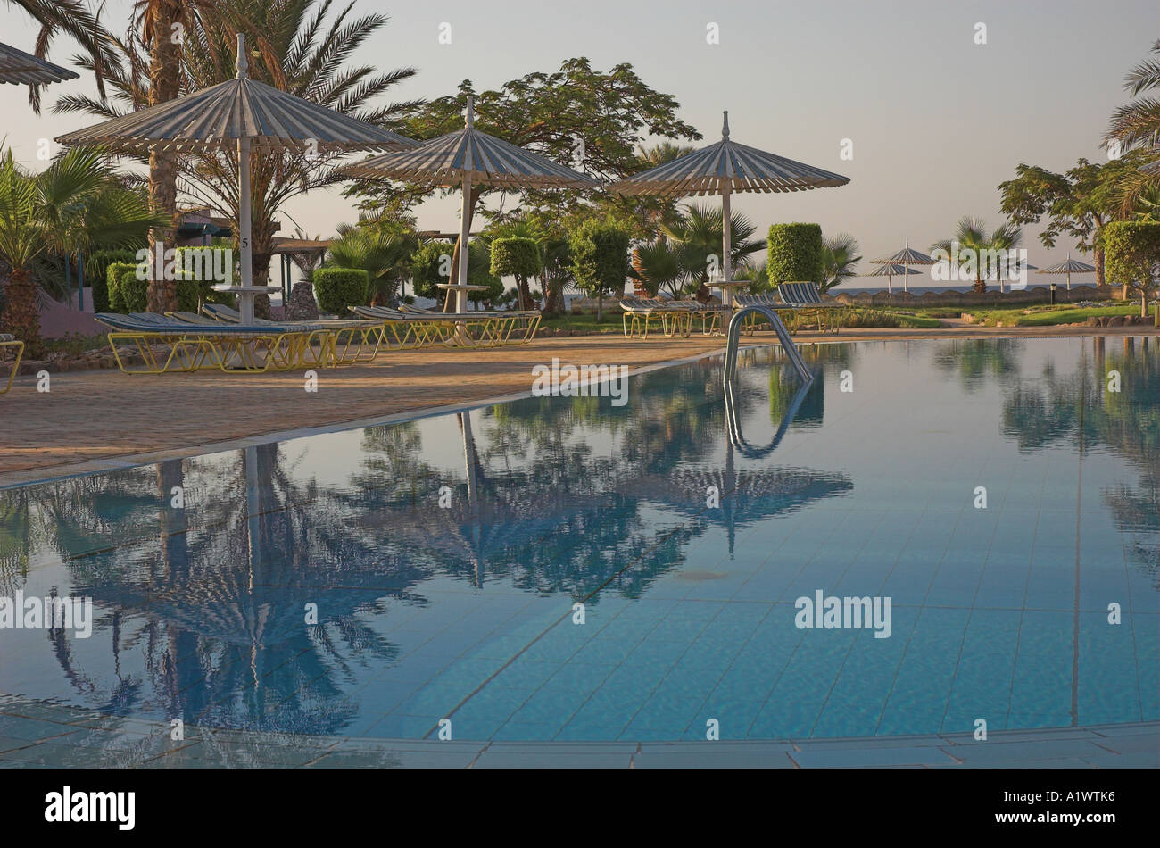 Deserted hotel swimming pool in the earling morning sunrise in Nuweiba Egypt - Stock Image