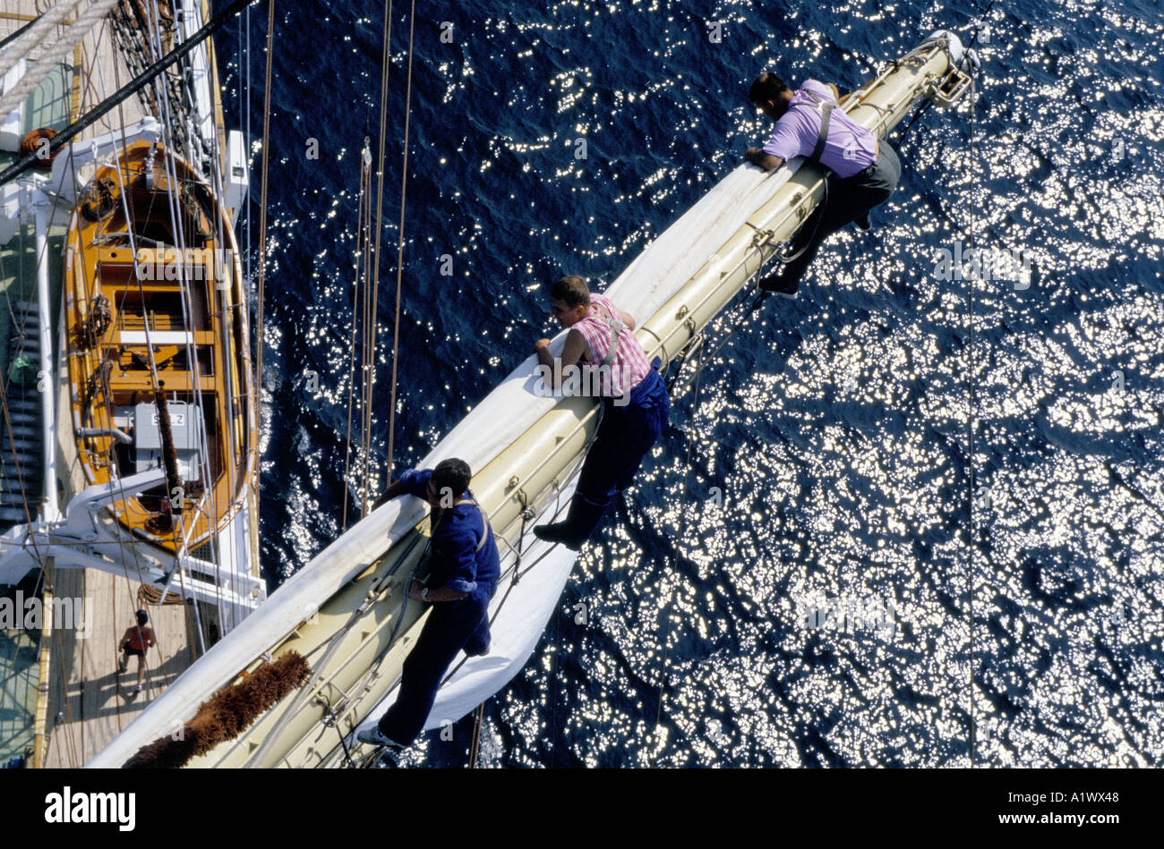 TALL SHIPS RACE 1994 CREWMEN ATOP MAST HAULING SAILS ABOARD THE S V MLODZIEZY ONE OF THE HISTORIC SAILING SHIPS TAKING PART IN THE ANNUAL CUTTY SARK TALL SHIPS RACE AT SEA BETWEEN PORTSMOUTH ENGLAND LA CORUNA SPAIN - Stock Image